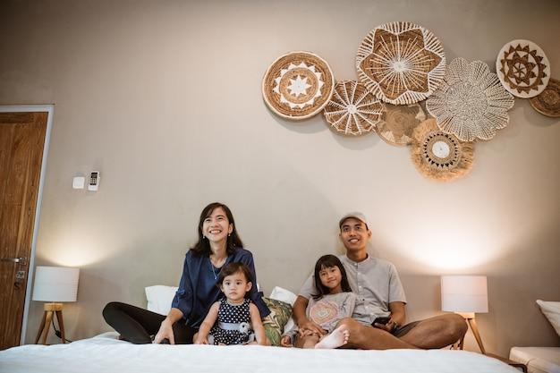 두 자녀와 함께 행복한 아시아 가족은 침실에서 함께 시간을 보냅니다.