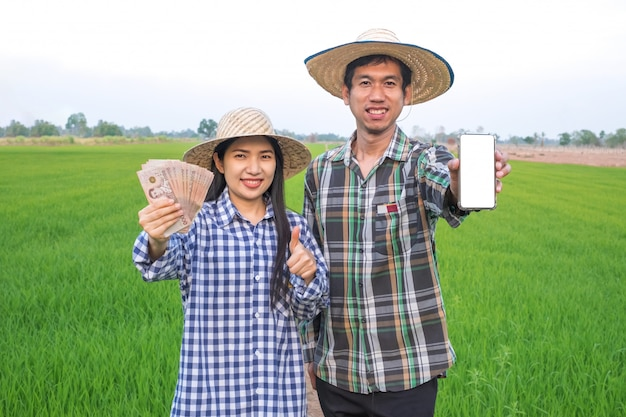 Happy asian farmer couple holding thai banknote and smartphone with blank screen standing at rice farm