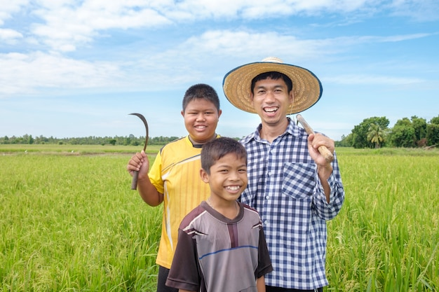 Happy asian farmer man and two kids smile and holding tools at green rice field
