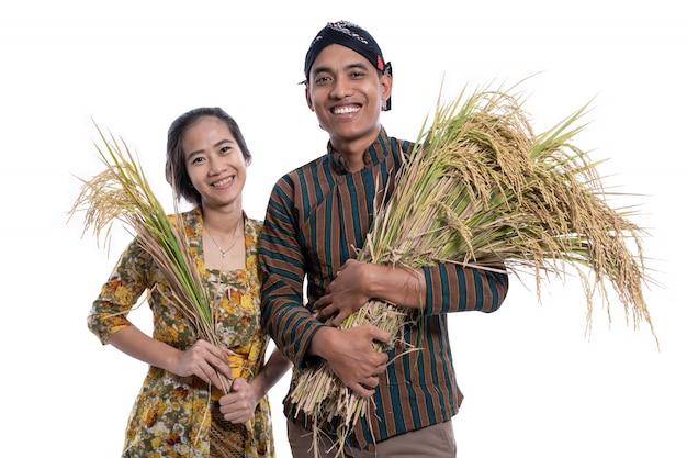 米粒を保持している幸せなアジアの農家