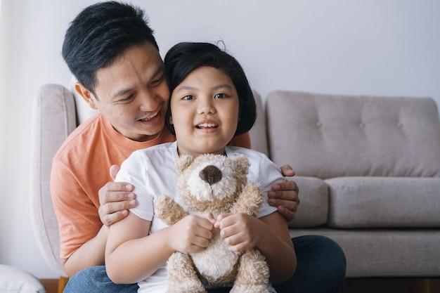 幸せなアジアの父と娘が自宅のリビングルームで一緒に遊んで。かわいい女の子は人形を抱きしめ、父親と一緒に幸せそうに笑います。