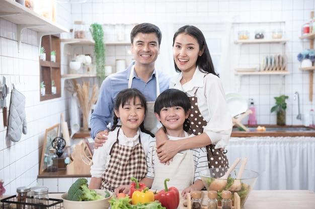 幸せなアジアの父、母、子に立って、キッチンで笑顔します。健康な親はサラダを準備します。
