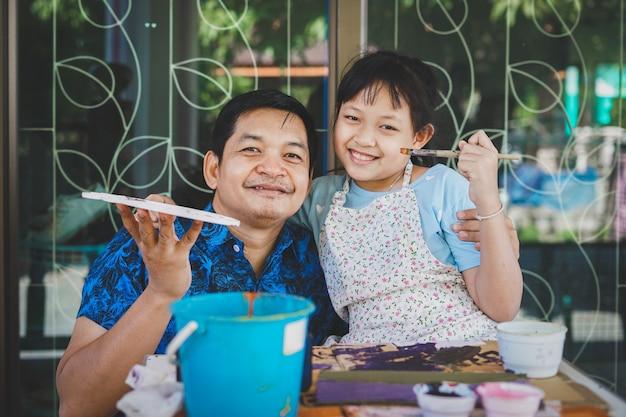 행복 한 아시아 아버지의 날. 재미있는 웃는 아버지와 그녀의 딸 그림과 수채화로 그리기