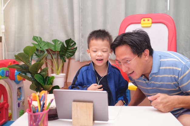 Happy asian father and son with tablet computer are making video call to mother or relatives at home