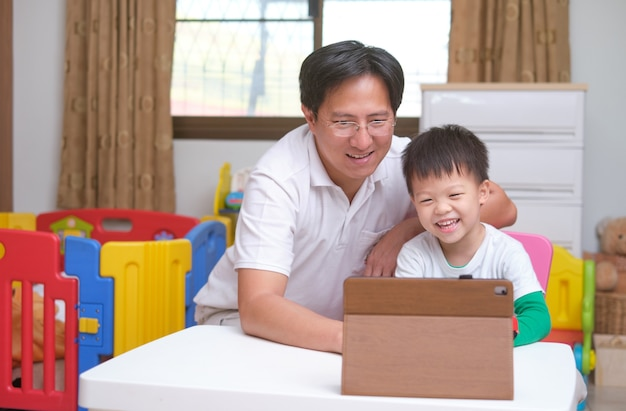 Happy asian father and son with tablet computer are making video call to mother or relatives at home,