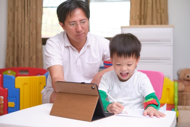 Happy asian father and son with tablet computer are studying online, attending school via e-learning