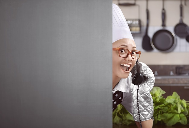Happy asian female chef lifted up the phone