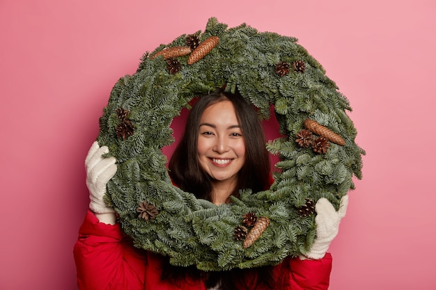 Happy asian female florist conducts master class how to make christmas home decorations, looks gladfully through handmade fur wreath