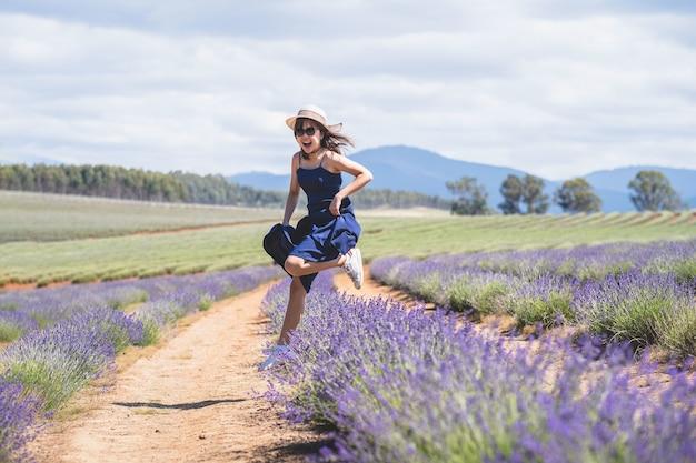 ラベンダー畑のカメラでポーズをとって長い青いドレスを着た幸せなアジアの女性