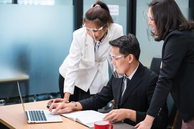 Счастливая азиатская женщина-менеджер консультирует и сотрудничает с коллегами, работающими с ноутбуком за столом в офисе