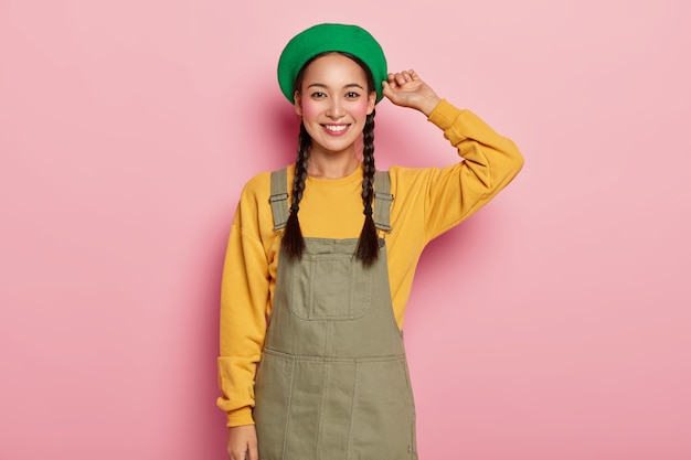 루즈 뺨을 가진 행복한 아시아 여성 모델, 즐거운 얼굴 표현, 세련된 베레모, 노란색 스웨트 셔츠 및 데님 사라 판 착용