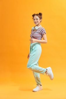 Happy asian female student jumping on yellow background