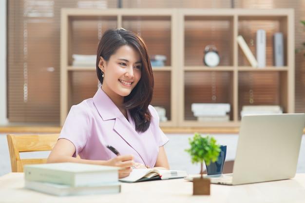 집에서 온라인으로 학습하는 노트북을 사용하여 노트북에 글을 쓰는 행복한 아시아 여학생