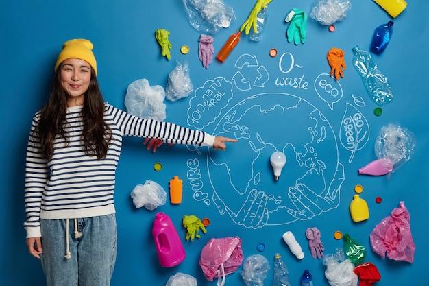 행복한 아시아 여성 자원 봉사자가 지구를 오염으로부터 구하는 방법에 대한 프로젝트를 준비하고 주변에 플라스틱 쓰레기로 그려진 행성을 보여줍니다.