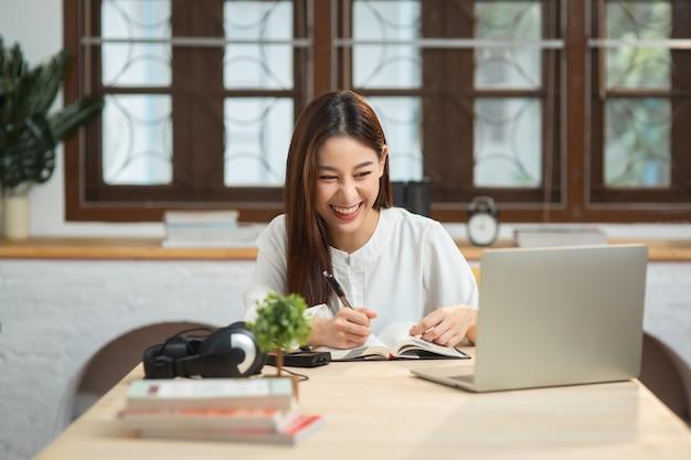 노트북에 글을 쓰는 행복한 아시아 여성은 홈 오피스에서 노트북 화면을 봅니다.