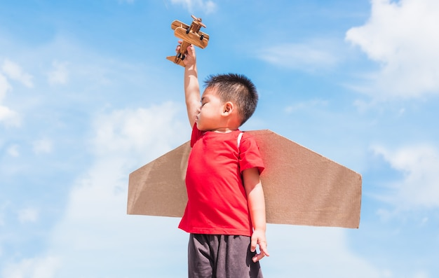 Happy asian funny child or kid little boy smile wear pilot hat play and goggles with toy cardboard airplane wing flying hold plane toy outdoor against summer blue sky cloud , startup freedom