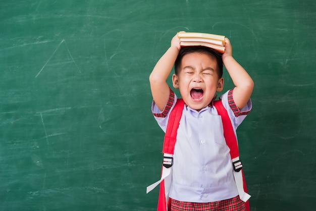 スクールバッグと緑の黒板の頭の上の本と学生服の幼稚園からの幸せなアジア面白いかわいい小さな子供男の子