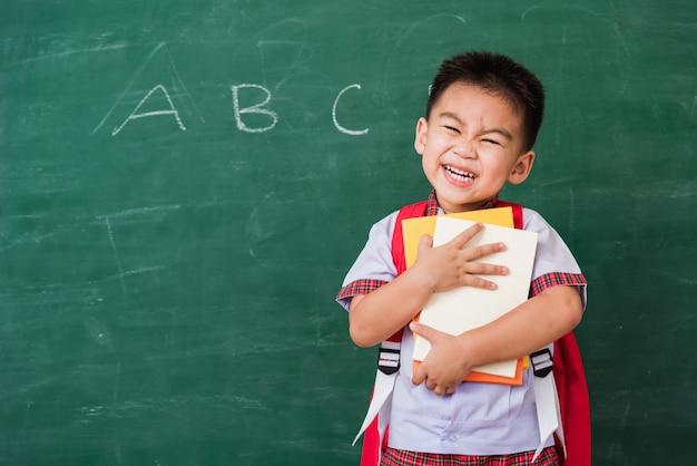 Happy asian funny cute little child boy from kindergarten in student uniform with school bag hugging the books smile on green school blackboard