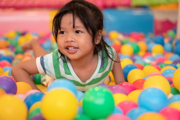 Happy asian girl (4 years olds) playing little colorful balls in pool ball. the  playing is the best learning for children.