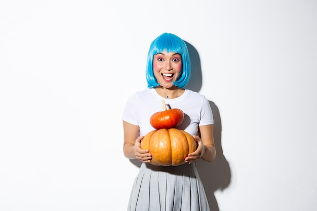 Happy asian girl in blue wig holding two cute pumpkins and smiling at camera, wearing schoolgirl outfit for halloween party.