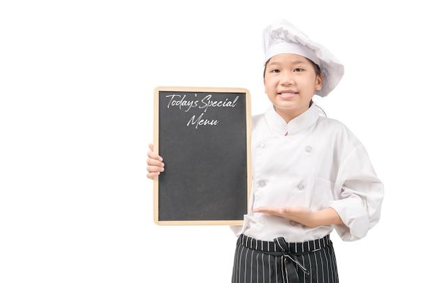 白い壁に分離された黒板に今日の特別メニューを提示する制服を着た幸せなアジアの女の子シェフ、入力テキストまたはコピースペース付きメニュー