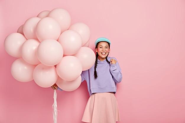 幸せなアジアの女の子は喜びで拳を握りしめ、特別な瞬間を待つことができず、彼女の誕生日に友人からお祝いを受け取り、愛らしい服を着て、たくさんの風船を運びます