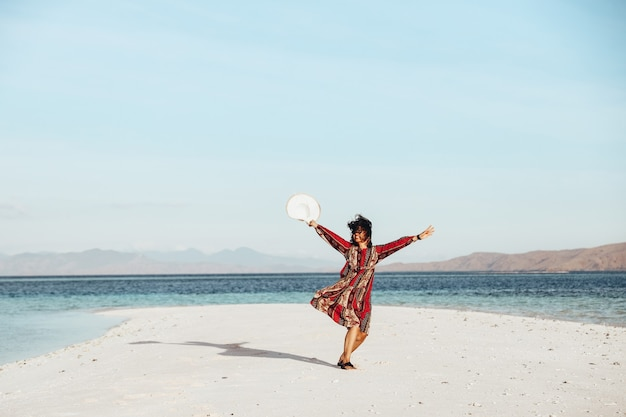 Happy asian girl dancing on white sand beach surounded by the sea