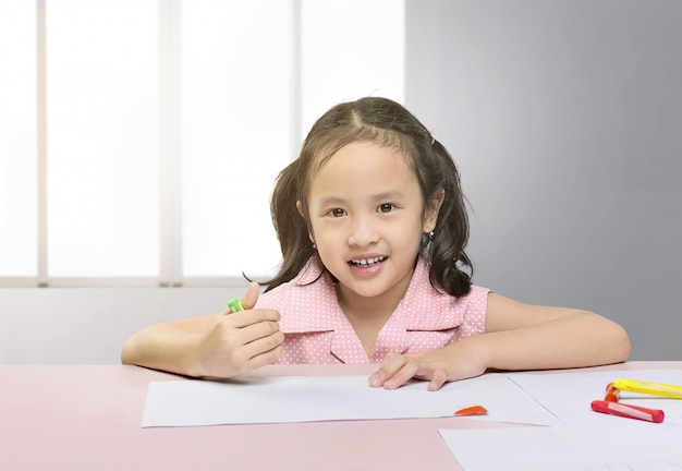 Happy asian girl drawing with crayon
