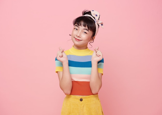 Happy asian girl hand showing mini heart gesture over pink background.