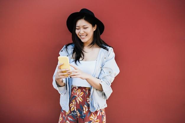 Счастливая азиатская девушка развлекается с помощью мобильного телефона на открытом воздухе в городе