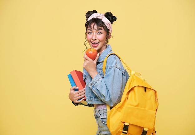 노란색 배경 위에 사과와 노트북을 들고 있는 행복한 아시아 소녀. 학교 개념으로 돌아가기.