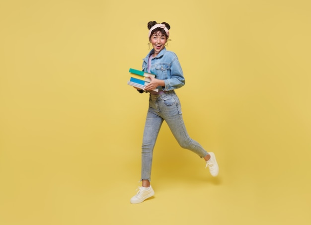 Happy asian girl holding book and jumping over yellow background. back to school concept.