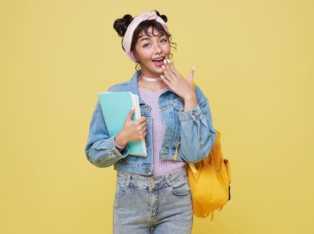 노란색 배경 위에 책가방을 들고 노트북을 들고 있는 행복한 아시아 소녀. 학교 개념으로 돌아가기.