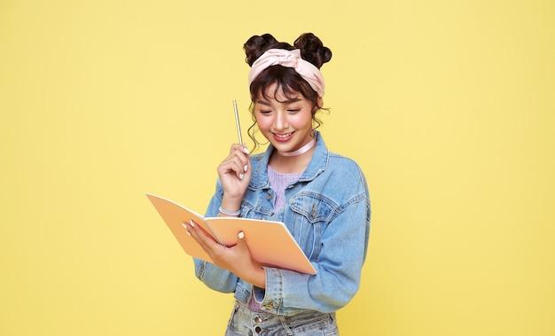 노란색 배경 위에 연필과 노트북을 들고 행복 아시아 소녀. 다시 학교 개념.