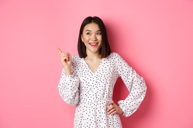 드레스를 입은 행복한 아시아 소녀가 왼쪽 상단 모서리에 만족한 손가락을 가리키며 웃고 있습니다.