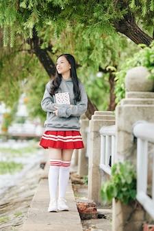 手に本を持って屋外に立っているパーカー、スカート、タイのハイソックスの制服を着た幸せなアジアの女の子