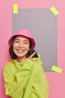 Felice ragazza asiatica indica che nello spazio vuoto per la vendita il logo sorride mostra positivamente qualcosa di piacevole sorride alla telecamera vestita con una felpa con cappuccio casual