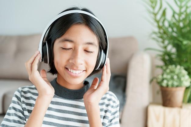 幸せなアジアの女の子は目を閉じてリビングルームに座っている間音楽です