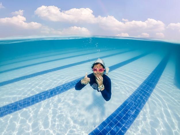 Happy asian girl love to swim underwater in swimming pool.