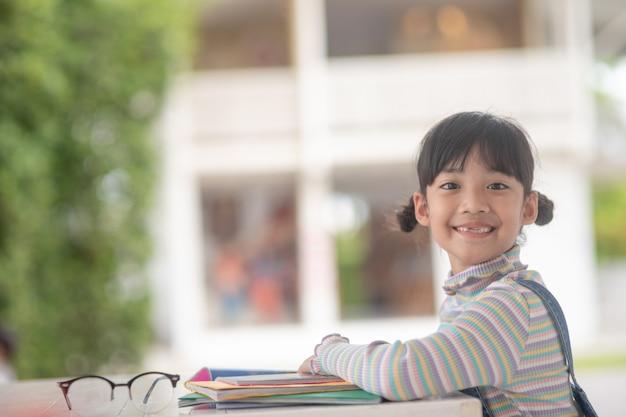 テーブルの上の物語の本を読んで幸せなアジアの女の子