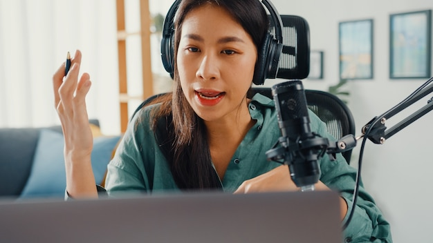 Happy asian girl recording a podcast on her laptop computer with headphones and microphone