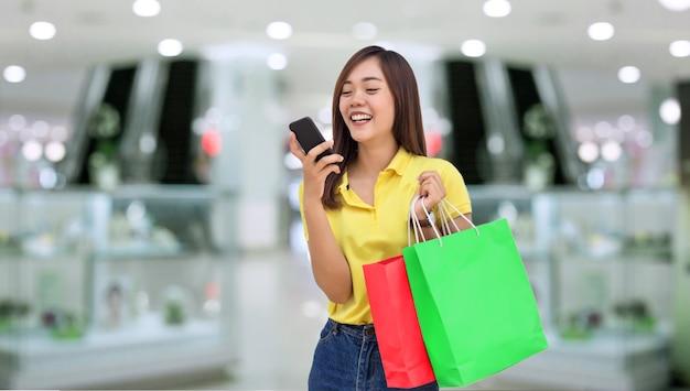 Счастливая азиатская девушка восстановила заказ на бумаге на сумке для покупок в черную пятницу, совершив покупки в интернете со смартфона и доставив домой в новом нормальном цифровом образе жизни.