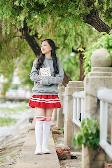 Happy asian girl in school uniform of hoodie, skirt and tigh high soks standing outdoors with book in hands
