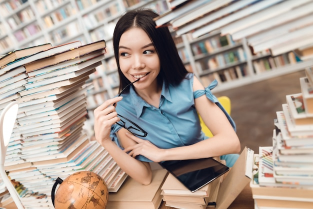 Happy asian girl sitting at table surrounded by books.