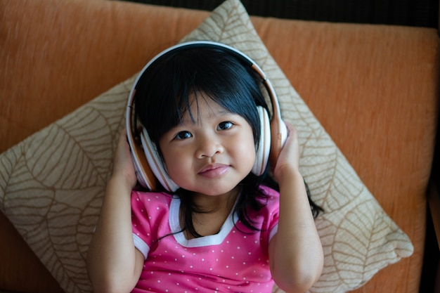 행복 한 아시아 여자 웃 고 즐기는 소파 거실에 헤드폰에서 음악을 듣는