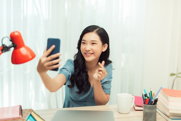 Happy asian girl smiling on video call phone, taking selfie on smartphone,