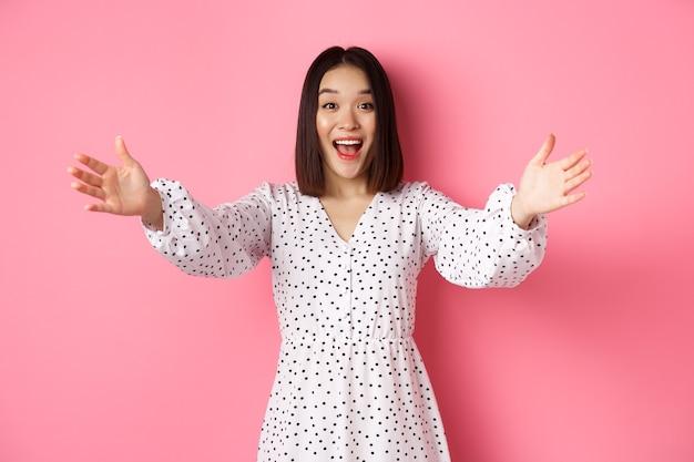 幸せなアジアの女の子がカメラに手を伸ばして抱擁の笑顔と何かを保持したいのですが...