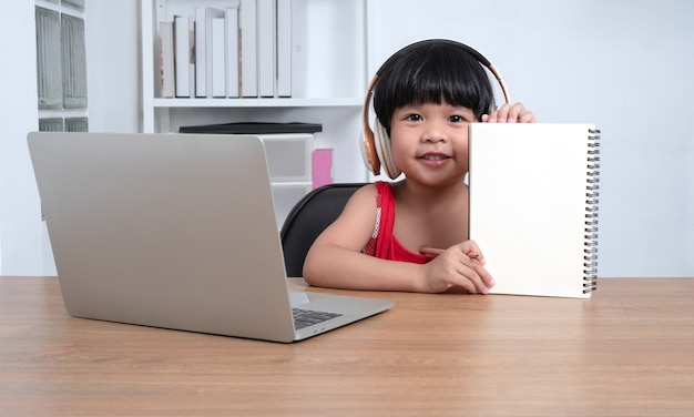 教師とコンピューターから幸せなアジアの女の子学生オンライン学習クラス