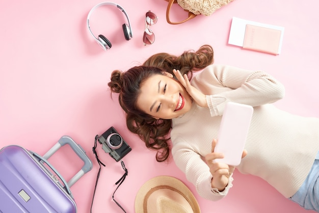 幸せなアジアの女の子が電話を使って写真を撮り、旅行荷物を持ってピンクの床に横になっている