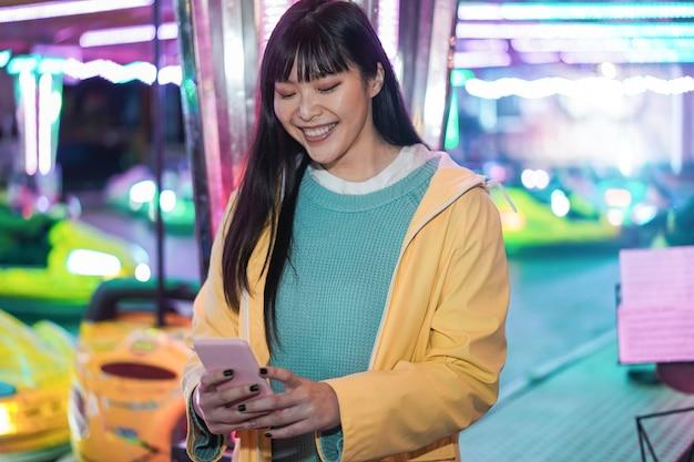 놀이 공원에서 스마트 폰을 사용 하여 행복 한 아시아 여자